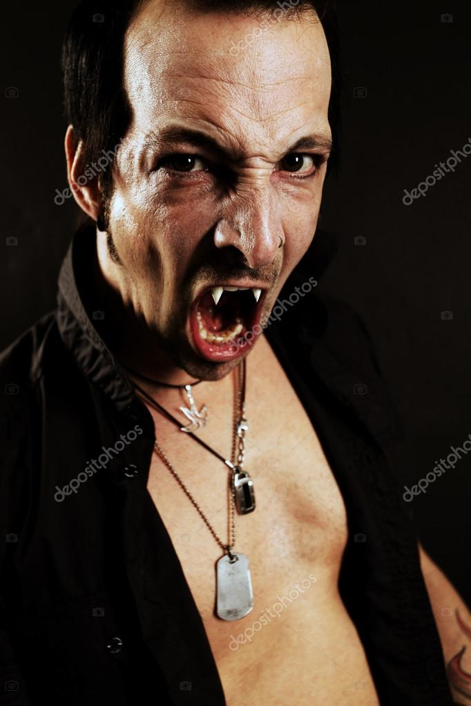 Photo of a male vampire with mouth open and fangs showing.  Harsh lighting and heavily filtered for scarier feel. — Stock Photo #13194267