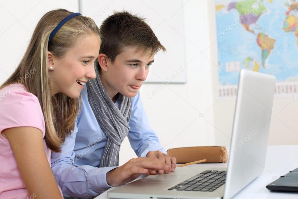 Photo of two students in their class working on a laptop.  Stock Photo #16174475
