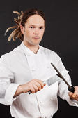 Handsome chef sharpening his knife — Stock Photo