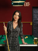 Beautiful brunette at a pool table — Stock Photo