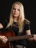 Attractive female playing acoustic guitar — Stock Photo