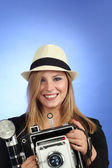 Blond woman pointing an old camera — Stock Photo