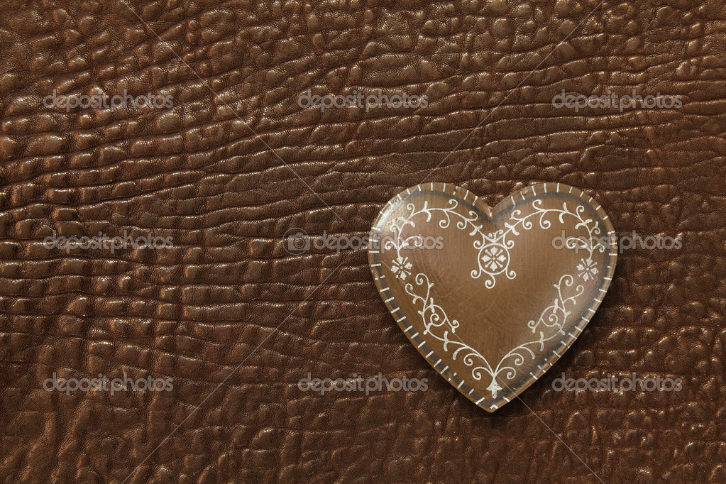 Photo of a metal heart on a dark brown leather background. — Stock Photo #20035333