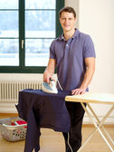 Attractive male ironing his shirt — Stock Photo