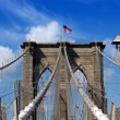 Foto Stock: Brooklyn Bridge and American flag