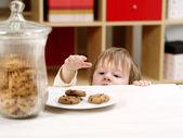 Little boy stealing cookies — Stock Photo