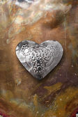Chrome metal heart on tarnished copper — Stock Photo