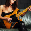 Beautiful guitarist sitting on couch — Stock Photo #28678181