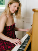 Adult female playing the piano — 图库照片
