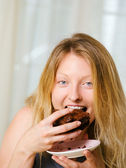 Blond woman biting a chocolate brownie — Stock Photo