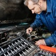 Mechanic fixing an engine — Stock Photo