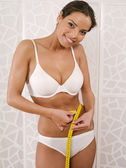 Woman in her underwear measuring her waist — Stock Photo