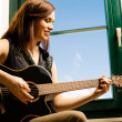 Smiling woman playing guitar by a window — Stock Photo #40690343
