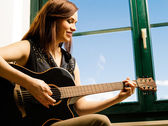 Smiling woman playing guitar by a window — Stock Photo