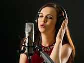 Singing into a studio microphone — Stock Photo