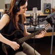 Woman with guitar in a recording studio — Foto de Stock