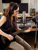 Woman with guitar in a recording studio — Stock Photo