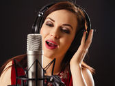 Singing into a professional microphone — Stock Photo