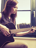 Playing acoustic guitar by the window — Stock Photo