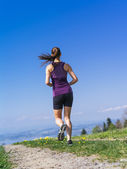 Young woman running on a country path — Stock Photo