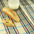 Baguette on a napkin whis milk — Stock Photo