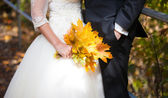 Bride and groom holding a golden leaves bouquet — Stock Photo