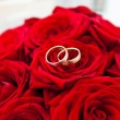 Wedding rings on red roses wedding bouquet — Stock Photo #20122331