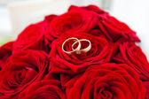 Obrączki na czerwonych róż, bukiet ślubny — Zdjęcie stockowe