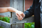 Young married couple holding hands on wedding day — Stock Photo
