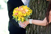 Young married couple holding hands with wedding bouquet — Stock Photo
