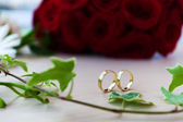 Wedding rings and white roses wedding bouquet — Stock Photo