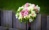 Wedding bouquet on rustic country fence — Stock Photo
