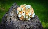 Wedding yellow roses bouquet on rock — Stock Photo