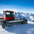 Snow-grooming machine on snow hill — Stock Photo