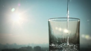 Conceptual footage of pouring water on a background of blurred city and sun, full HD — Stock Video
