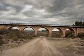 Stone bridge and dirt road — Stock fotografie