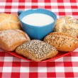 Milk in cup and various rolls — Stock Photo