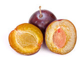 Whole and half plums — Stock Photo