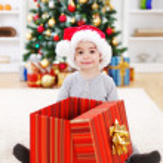 Happy boy sitting behind big present — Stock Photo #8003325