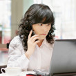 Woman using a laptop computer and phone — Stock Photo #3068531