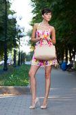 Happy beautiful model standing on street.flowered white dress .beige leather handbag. high heels — Stock Photo