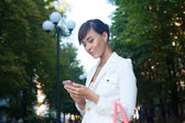 Beautiful model in white jacket dealing phone number on the street — Stock Photo