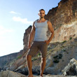 Ftnesst body guy on seashore on rocks. grey T-shirt, brown trousers — Stock Photo