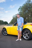 Trendy male model posing near open roof car on the road — Stock Photo