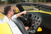 Stylish man steering yellow cabrio. interior of the vehicle. top view — Stock Photo