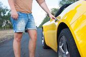 Closeup de joven abre puerta de coches covertible. coche amarillo. camiseta marrón, pantalones vaqueros — Foto de Stock