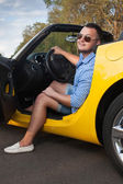 Lucky young man sitting in his new convertible car — Stock Photo