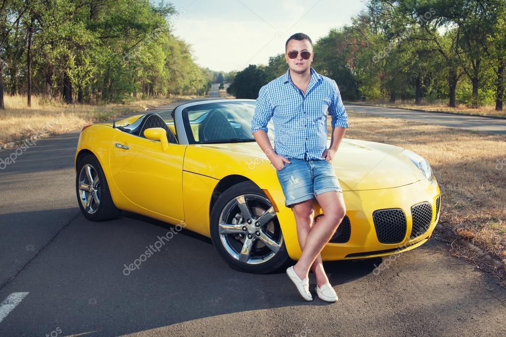jeune conducteur debout pr s de sa voiture de sport photographie arastorguev 30737005. Black Bedroom Furniture Sets. Home Design Ideas