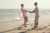 A heart shape drawn in the sand. Couple standing inside heart picture on the sand. Summertime fun — Stock Photo