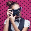 Portrait of beautiful hipster style young woman in white shirt and bow-tie. Old camera hanging by the neck — Stock Photo #36029897